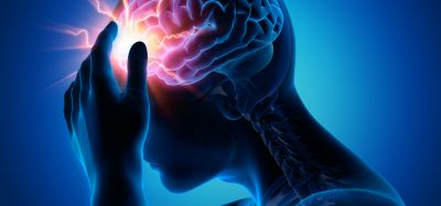 man holding the front of his head with the temporal lobe of the brain highlighted in red