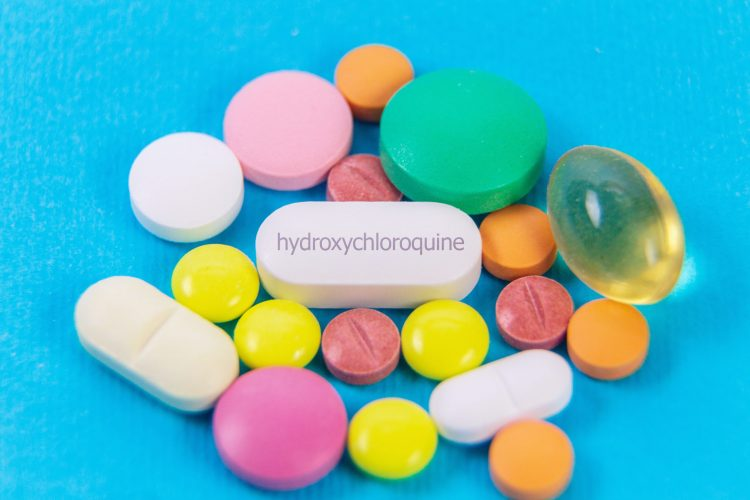 pile of colourful medication tablets with a central white tablet labelled 'hydroxychloroquine'