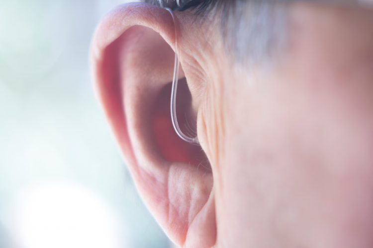 close up of a man's ear with a hearing aid in - idea of deafness