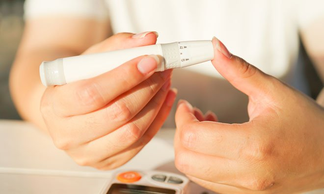 Diabetic woman checking blood sugar level using Glucose Meter