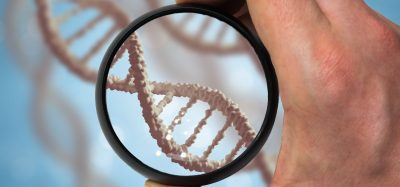hand holding a black rimmed magnifying glass over a DNA strand - idea of genetic research