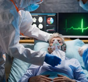 patient on a ventilator surrounded by monitors and doctors wearing personal protective equipment