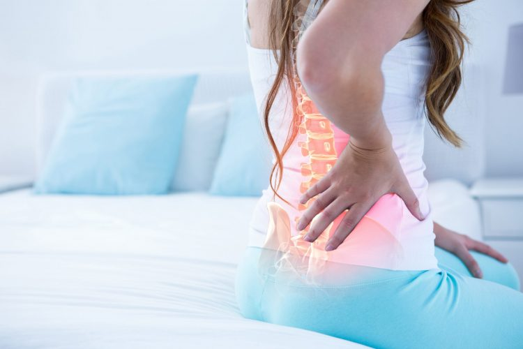woman holding back with spine highlighted in red